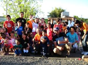 Roselaine (sentada, de preto) e Paulo (com a câmera, de laranja) com voluntários, crianças e pais